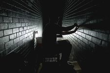 Free Person In Between Grey Bricks Wall Trying To Attach Bricks With Single Led Light Stock Photos - 83012553