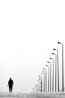 Free Man Walking Near Aligned Lamp Post Royalty Free Stock Photo - 83014725