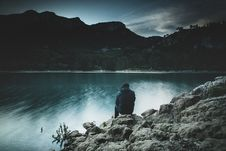 Free Man Sitting At Mountain Lake Stock Photography - 83015132
