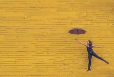 Free Woman In Black Tank Top Holding An Umbrella In Front Of Yellow Concrete Wall Stock Photo - 83015620
