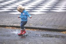 Free Boy In Blue Jacket Hopping On Water Puddle Stock Photography - 83017422