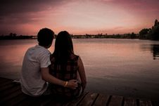 Free Man And Woman Sitting At Wooden Surface With Man S Hand On Woman S Waist Looking At Sunset Beside A Lake Royalty Free Stock Photos - 83019948