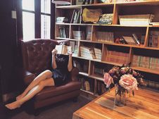Free Woman In Black Mini Dress Sitting On Brown Leather Tufted Sofa Chair Beside Brown Wooden Book Shelf Royalty Free Stock Images - 83025859