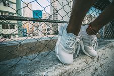 Free Person Wearing White Adidas Low Top Shoe Near Gray Cyclone Fence Royalty Free Stock Image - 83037486