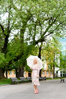 Free Woman In White Green And Red Floral Holding White Umbrella On Gray Concrete Pathway Near Brown Wooden Bench Near Trees During Dayt Stock Photos - 83037573