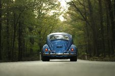 Free Blue Beetle Car On Gray Asphalt Road Between Green Leaf Trees Royalty Free Stock Photos - 83058728