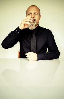 Free Man In Black Dress Shirt Sitting In Front Of White Table Drinking Water Stock Photos - 83059023