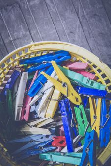 Free Red Blue Teal Green And Yellow Clothes Pin In Yellow Plastic Bucket Stock Photo - 83059500