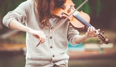 Free Woman In Gray Cardigan Playing A Violin During Daytime Stock Images - 83059514
