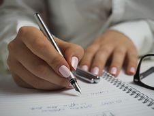 Free Woman In White Long Sleeved Shirt Holding A Pen Writing On A Paper Royalty Free Stock Images - 83059529