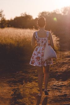Free Woman In White And Pink Floral Sleeveless Dress Walking On Brown Road During Sunlight Royalty Free Stock Image - 83059666
