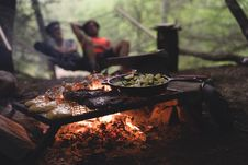 Free Black Non Stick Pan On Black Metal Charcoal Griller With Steak On Outdoor Forest With Two Persons Seating On Hammock Stock Photography - 83059732
