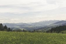 Free Green Grass Field Under Grey Clear Sky Overlooking Mountains Stock Photos - 83059893