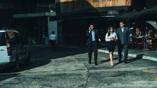 Free Woman In White Dress Shirt Between Men In Suit Standing On Concrete Ground Stock Image - 83059961