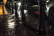 Free Black Posts On Black Pavement Beneath Falling Rain Stock Photos - 83060123