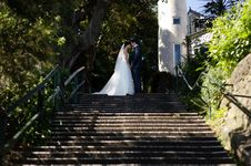 Free Couple Kissing After Wedding Near Stair Beside Garden Stock Photography - 83060212