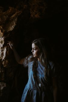 Free Woman In Blue Denim Jumpsuit Leaning On Brown Rock Stock Images - 83060554