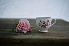 Free White And Pink Rose Print Ceramic Cup Near Pink Rose On Brown Wooden Table Royalty Free Stock Photo - 83060655