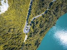Free Aerial View Of Curved Road Between Green Leaf Trees Near Ocean Royalty Free Stock Photo - 83061005