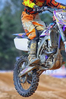 Free Person In Orange And Yellow Fox Motorcycle Suit Riding A Purple White Gray And Black Dirt Motorcycle Outdoors During Daytime Royalty Free Stock Photography - 83062247