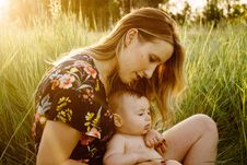 Free Blonde Haired Woman In Black Green Yellow And Teal Floral Scoop Neck T-shirt Holding Black Haired Baby On Green Grass During Sunri Stock Image - 83062341