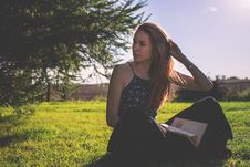 Free Woman In Black Tank Top And Holding Brown Book Sitting On Grass Under Clear Sunny Sky Stock Image - 83062391