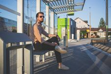 Free Man Wearing Sunglasses Sitting At Bus Stop During Daytime Royalty Free Stock Photos - 83062428