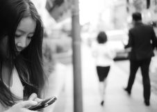 Free Woman Using Smartphone At Sidewalk Near Man And Woman Walking Away From Her Royalty Free Stock Images - 83062719
