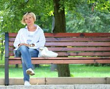 Free Thinking Woman In White Jacket And White Scoop Neck Shirt Blue Denim Jeans Sitting On Brown Wooden Bench Beside Green Trees During Stock Photos - 83062823