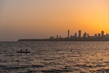 Free 2 Person On The Boat On The Ocean In Front Urban City During Golden Hour Royalty Free Stock Images - 83062999