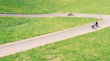 Free People Walking And Biking On The Concrete Roadway In Middle Of Green Plain Fields Royalty Free Stock Images - 83063029
