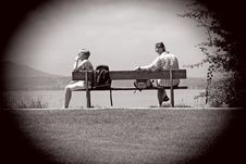 Free Man Sitting On Other Edge Of Bench Parallel To Woman With Bags In Between Them Stock Images - 83063184