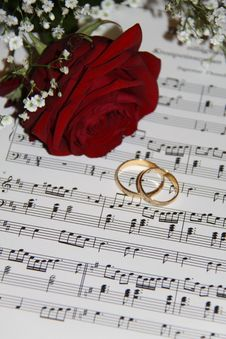 Free 2 Gold Eternity Ring Near Red Rose On Musical Notes Stock Photos - 83063343