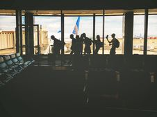 Free Group Of People Walking Near Clear Glass Window With A View Of White Airplane Parked During Daytime Royalty Free Stock Photos - 83063398