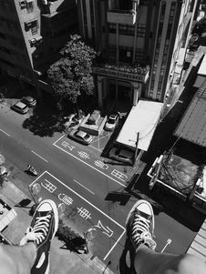 Free Grayscale Photography Man Wearing All Star Converse High Tops Below In Street And Building Royalty Free Stock Images - 83063949