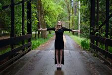 Free Woman In Black Long Sleeve Dress Standing On Black Bridge In The Forest Leaning Sky During Daytime Stock Images - 83064244