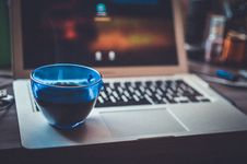 Free Blue Glass Cup On Silver Laptop Computer Royalty Free Stock Photos - 83064268