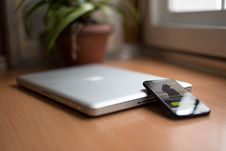 Free Smartphone Beside Silver Macbook On Brown Wooden Table With Potted Plant In The Background Stock Photos - 83064563