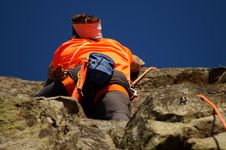 Free Person In Orange Shirt Climbing Rock During Daytime Stock Image - 83064731