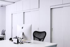 Free Black Mesh Office Rolling Chair Beside White Wooden Desk With White Imac Royalty Free Stock Image - 83064736