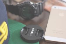 Free Canon Lens Cover Beside Gold Iphone 5s And Casio G Shock Chronograph Watch Stock Photo - 83064760