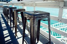 Free Row Of Stool By Water Stock Images - 83065184