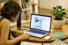 Free Woman In Black Tank Shirt Facing A Black Laptop Computer On Brown Wooden Round Table Stock Images - 83065314