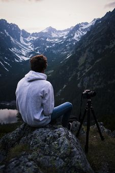 Free Man In Gray Hoodie Sitting On Gray Stone With Dslr Camera Tripod Royalty Free Stock Image - 83065446