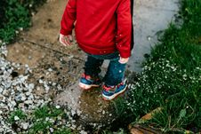 Free Boy In Red Jacket Jumping On Concrete Walkway Near Grass During Daytime Stock Photo - 83065540