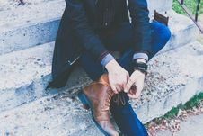 Free Person Wearing Black Jacket Blue Jeans And Brown Leather Boots Sitting On Gray Concrete Stairs During Daytime Stock Photo - 83065880
