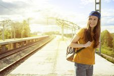 Free Smiling Woman In Orange T Shirt And Blue Snap Back Cap Carrying Backpack Stock Image - 83065951