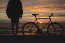 Free Silhouette Photo Of A Person Beside A Mountain Bike Near The Sea At Sunset Royalty Free Stock Photos - 83066038
