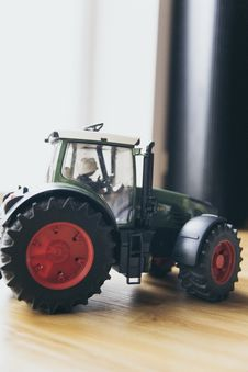 Free Black And Green Farm Tractor Toy On Brown Wooden Table Beside Window Stock Images - 83074134