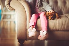 Free Girl In Grey Jacket And Pink Jeans Sitting In Grey Sofa Holding A Brown Short Coated Puppy Stock Images - 83074594